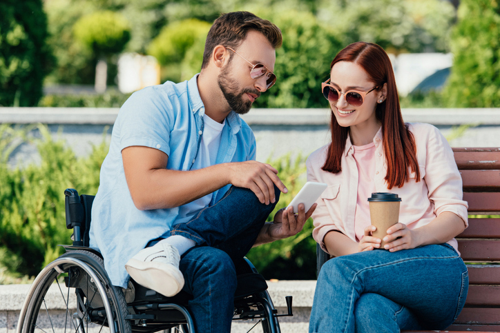 young man in wheelchair looks at cell phone with young woman on park bench