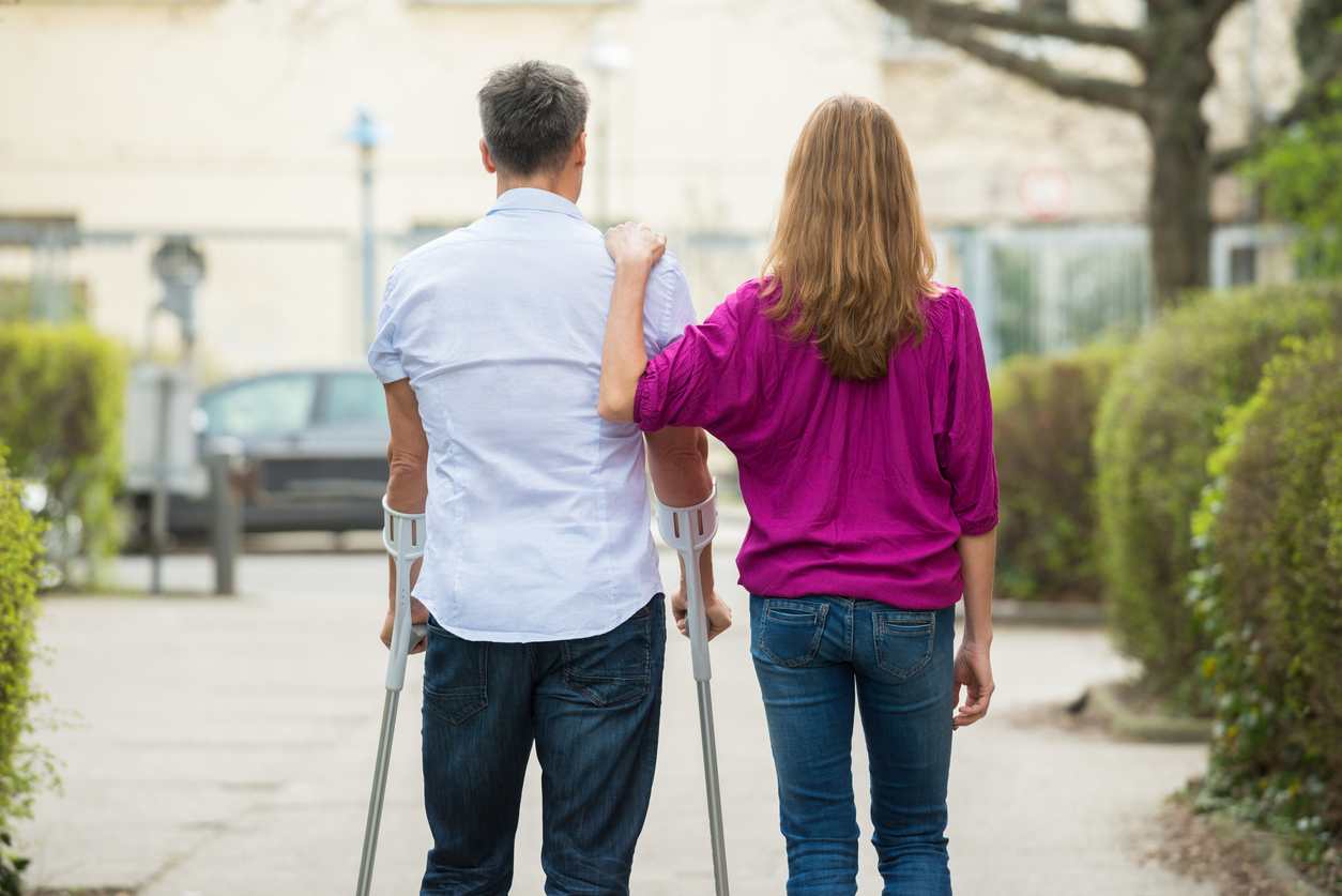 young woman with hand on shoulder of a man using crutches