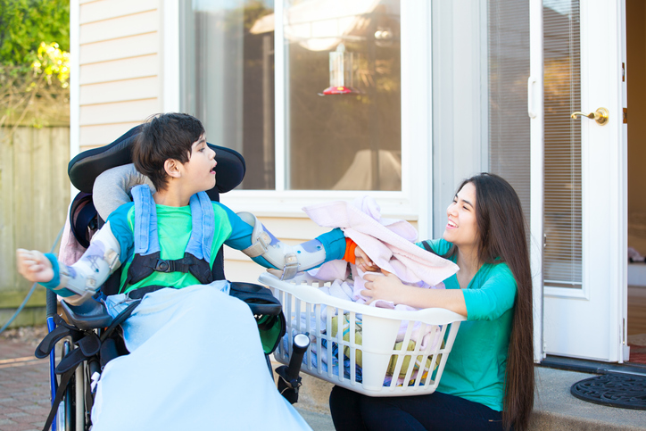 young woman and child in wheelchair do laundry outside