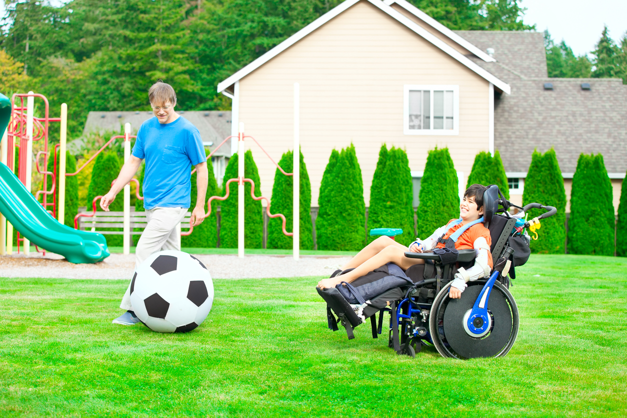 young child in wheel chair plays soccer with an adult with a large inflatable soccer ball