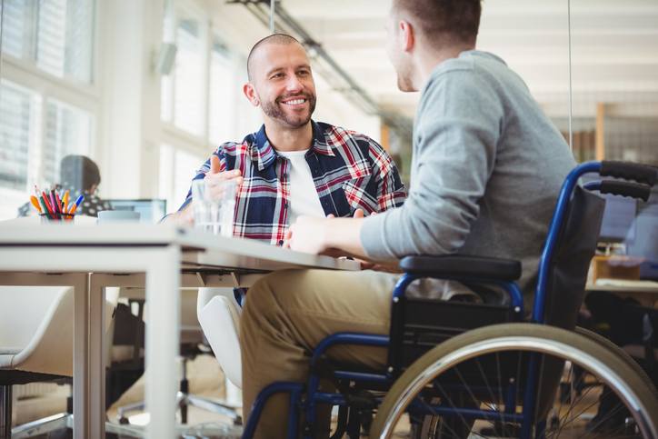 young man in wheelchair works with another young man at an office desk