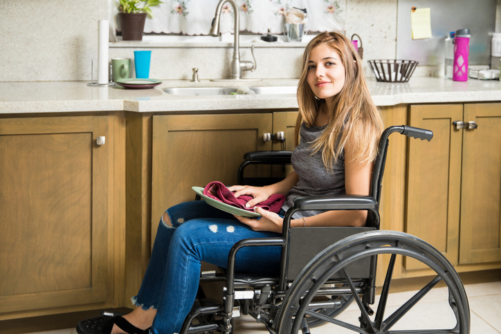 young woman in wheelchair washes dishes near the kitchen sink