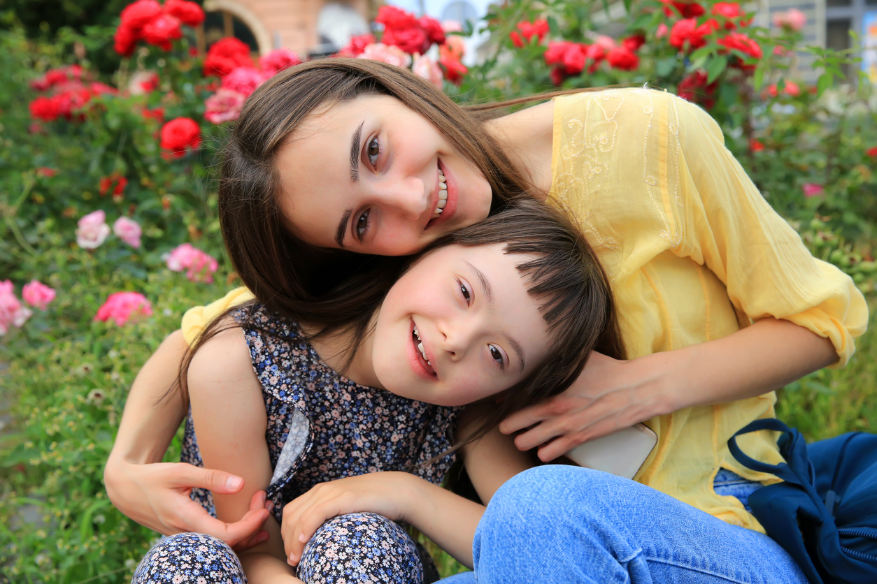 young woman and down syndrome child smile in a garden