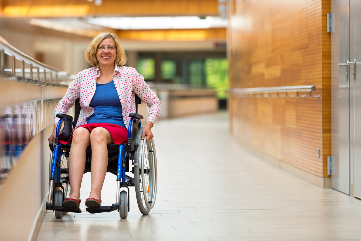 professional woman in wheel chair smiles while in a corporate setting