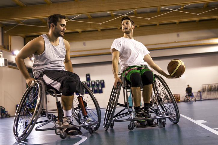 two men in wheelchairs playing basketball in a gym