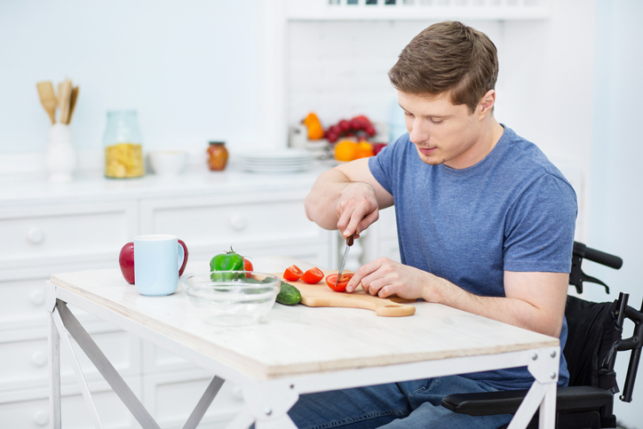 young man in wheelchair prepares dinner in a kitchen